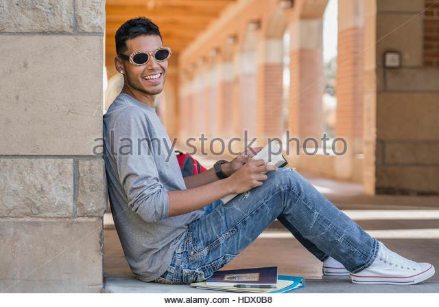 Hispanic man leaning on wall reading book wearing sunglasses - Stock Image