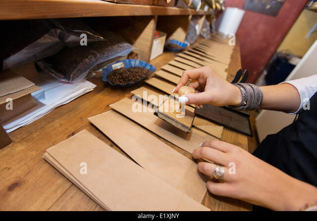 Cropped image of salesperson stamping paper bags at coffee store - Stock Image