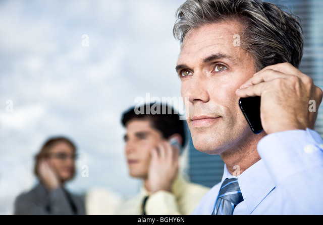 A mature business man and his team talk on mobile phones outside - Stock Image