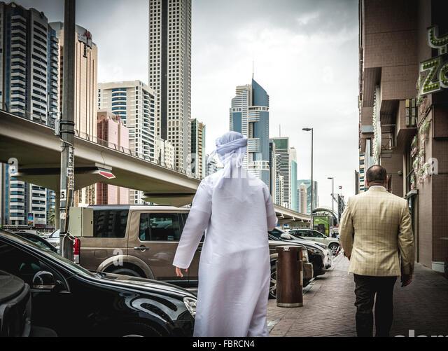 Arab man walking along busy Sheik Zayed Road - Stock-Bilder