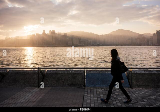 Side view of young woman walking past water, Hong Kong, China - Stock-Bilder