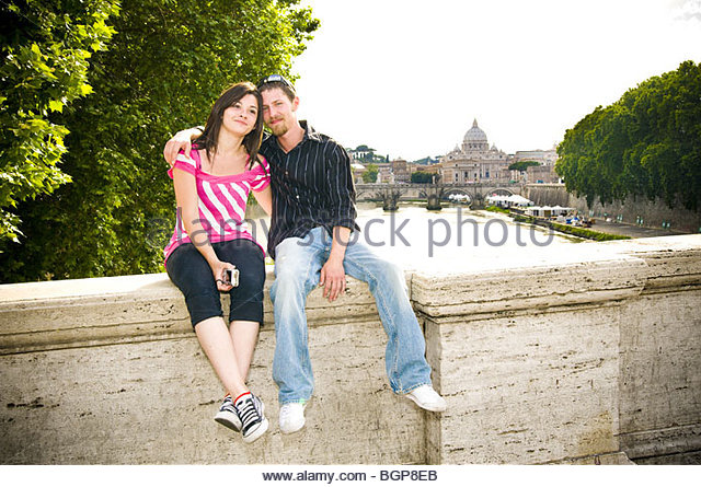 Portrait of young couple sitting on ledge with Saint Peter's Basilica behind, - Stock Image