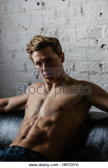 Shirtless young man reclining on a couch - Stock Image