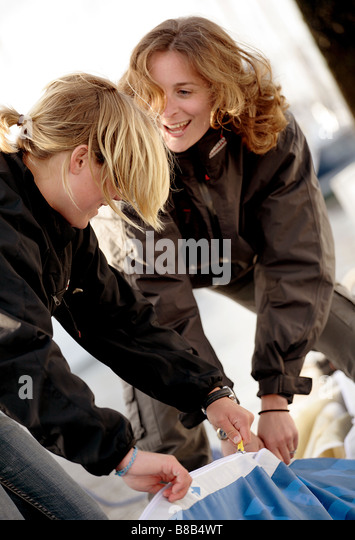 2 female sailors preparing the rigging for a journey,the woman are 20-30 in age and are laughing. - Stock Image