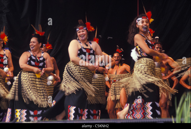 A Maori Concert Party singing and dancing on stage, the women at the front with pois, the men behind - Stock Image