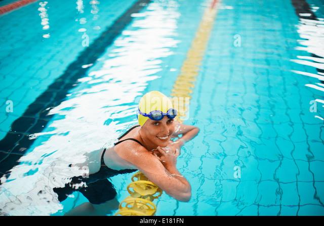 Portrait of smiling swimmer leaning on swimming lane marker in pool - Stock-Bilder