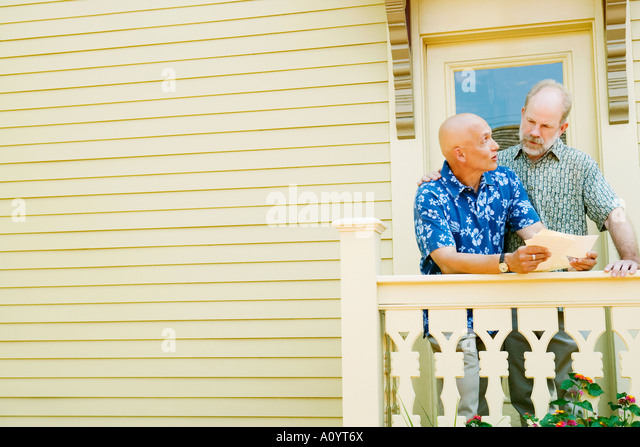Couple reading their mail on porch - Stock-Bilder