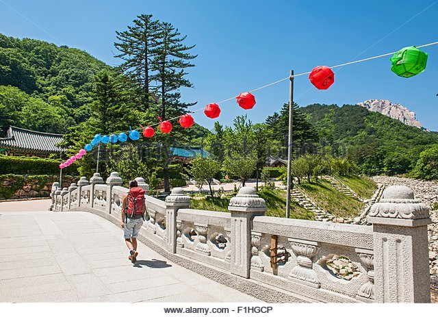 Woman hiking over a stone bridge on the way to Mt. Ulsanbawi at Seoraksan national park, Gangwon, South Korea - Stock Image