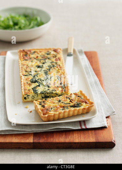 Plate of egg quiche on wooden board - Stock Image