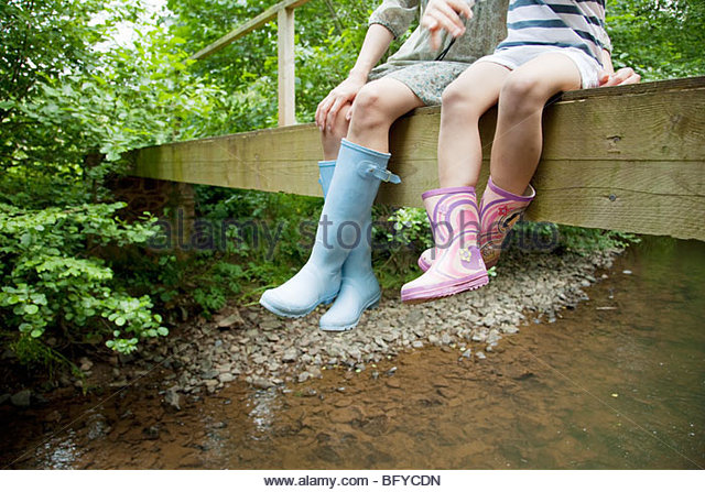 Mother and daughter sitting on bridge - Stock Image
