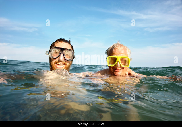 Portrait of two men swimming in sea - Stock-Bilder