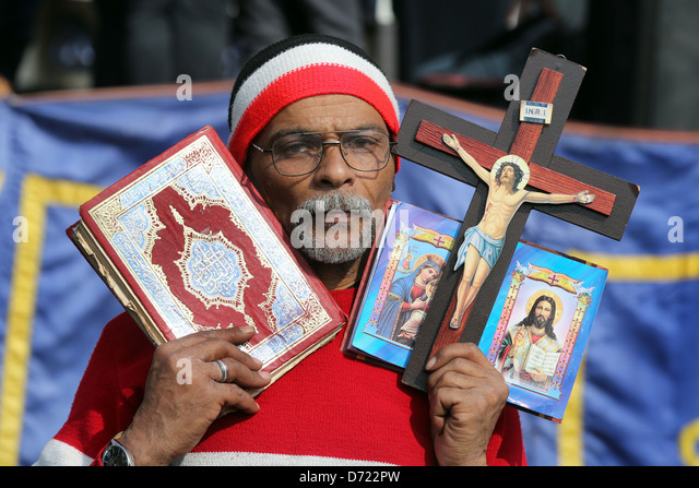 An Egyptian man holds the holy Koran and a christian bible with wooden cross during a mass rally in Tahrir Square, - Stock-Bilder