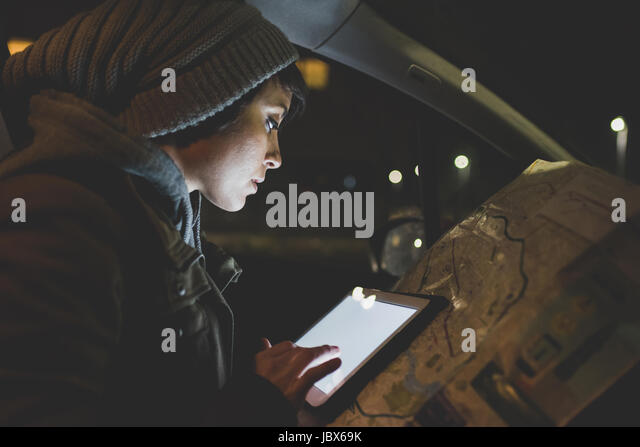 Woman in car front seat using digital tablet touchscreen in city at night - Stock-Bilder