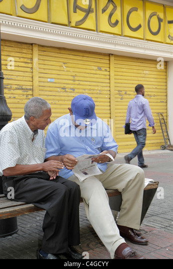 Santo Domingo Dominican Republic Ciudad Colonia Calle el Conde Peatonal pedestrian mall bench Hispanic man sitting - Stock Image