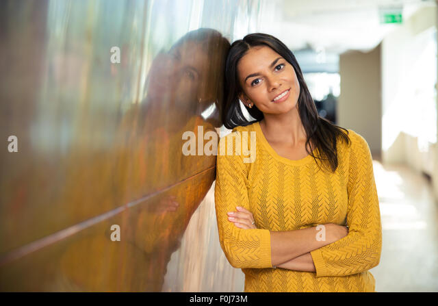 Portrait of a cheerful businesswoman standing with arms folded in hallway - Stock Image