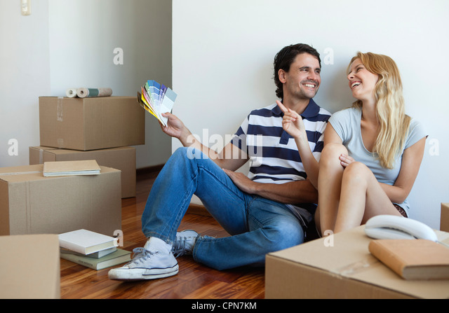 Couple discussing color swatches in new house - Stock Image