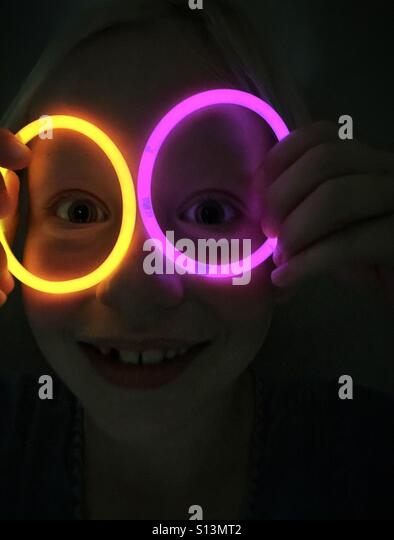 A child resembles a clown with glow sticks encircling eyes in a dark room. - Stock Image