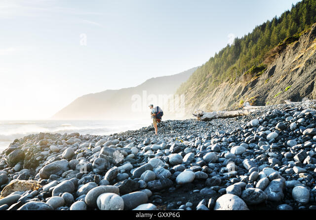 A lone backpacker gazes into the sea while trekking along Northern California's Lost Coast - Stock Image