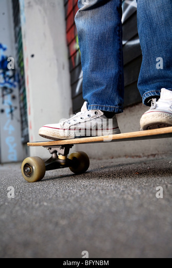detail of young boy standing on skateboard - Stock Image