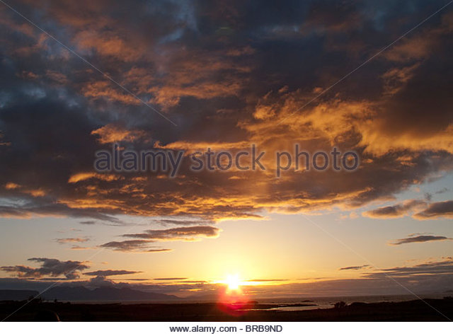 Sunset over land and ocean - Stock Image