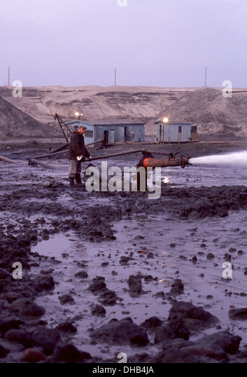Workman sprays a water canon at the Blue Clay inside the open pit Palmnicken Amber Mine on the Baltic Sea, Russia - Stock Image