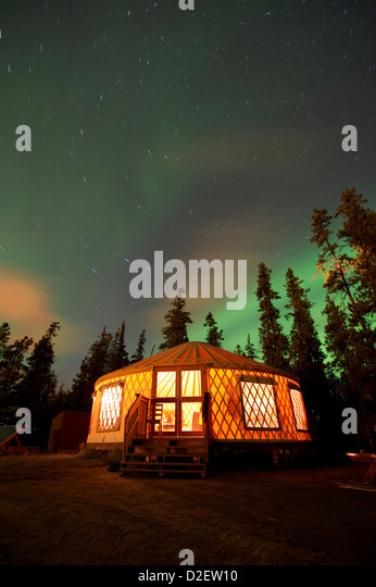The Aurora Borealis (Northern Lights) over an illuminated yurt outside of Whitehorse in the Yukon Territory, Canada. - Stock Image