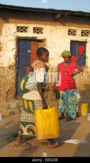 women at the poor area of the capital city taking water to their homes in canisters, baby is sleeping on its mother's - Stock Image