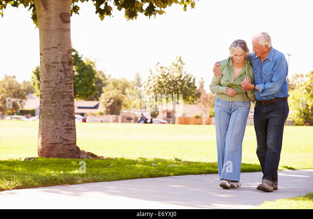 Senior Man Helping Wife As They Walk In Park Together - Stock Image