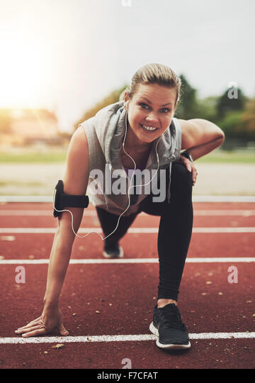 Young blonde sportswoman looking at camera while stretching on stadium before running, listening to music - Stock Image