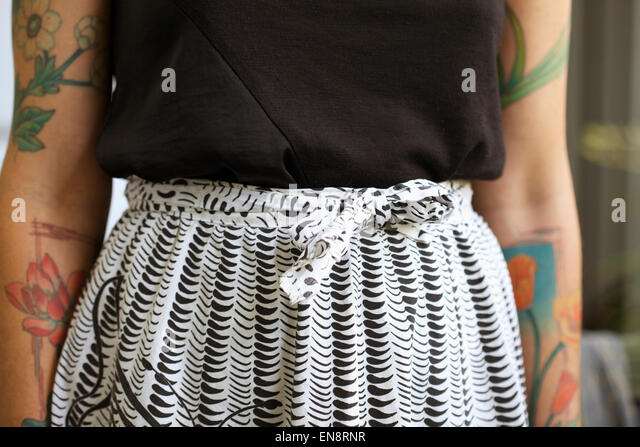 A woman's torso, she has colorful tattoos & is wearing a black shirt and a black and white vintage skirt - Stock Image