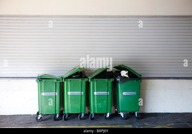 Overflowing garbage cans in a row - Stock Image