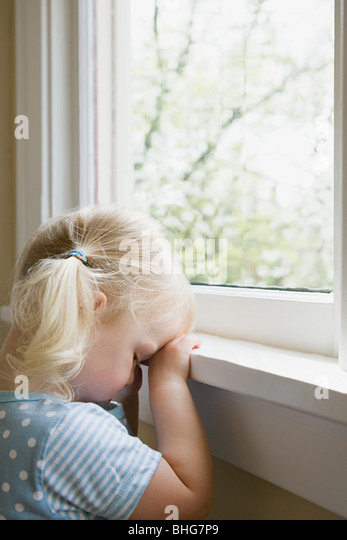 Sad little girl by window - Stock Image