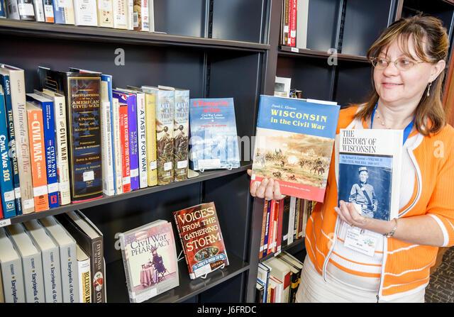 Wisconsin Kenosha Civil War Museum Resource Center librarian woman books history bookcase research - Stock Image