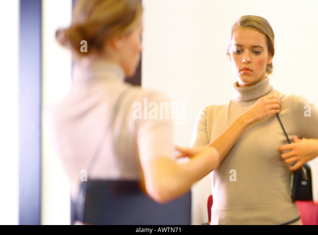 Woman looking in mirror at purse. - Stock Image