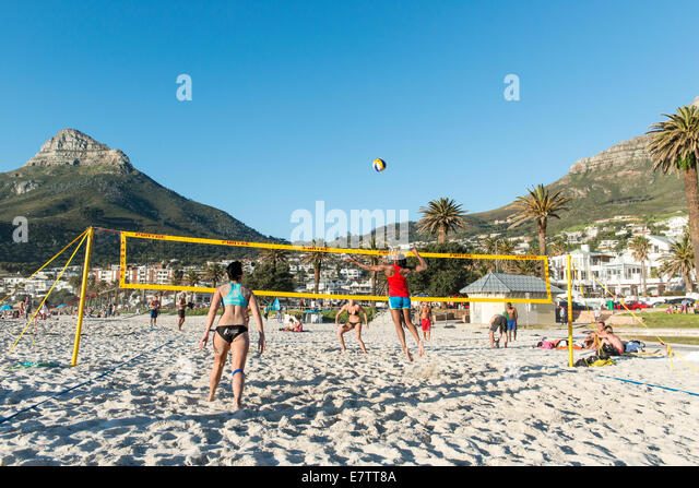 Beach volleyball players on the beach of Camps Bay, Cape Town, South Africa - Stock Image