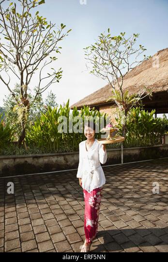 Balinese woman making morning offerings at Ubud Hanging Gardens, Bali, Indonesia. - Stock Image