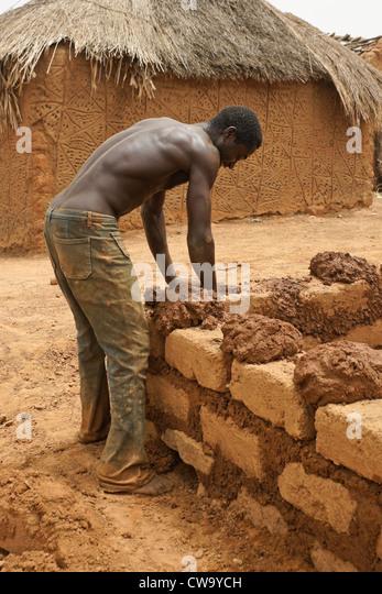 Man building mud-brick house in Mognori Eco-Village, Ghana - Stock Image