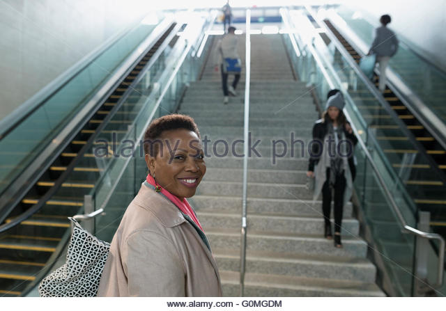 Portrait smiling woman in train station - Stock Image