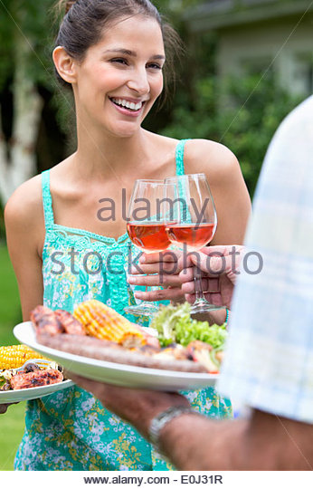 Smiling father and daughter holding plates of barbecue and toasting wine glasses - Stock Image