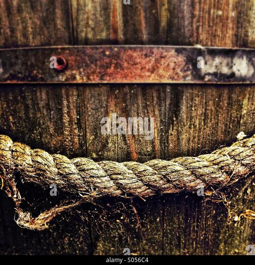 Side view of old wooden oak bucket planter with thick hessian rope handle - Stock Image