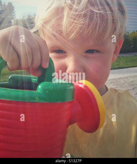 A young boy inspects his garden watering can. - Stock Image