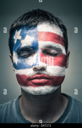 Portrait of man with USA flag painted on his face and closed eyes. - Stock Image