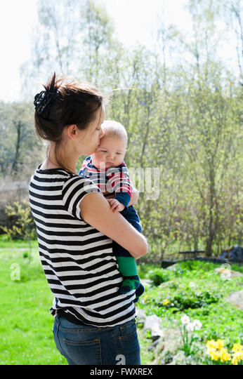 Sweden, Ostergotland, Vikbolandet, Woman carrying and kissing baby boy (6-11 months) - Stock Image