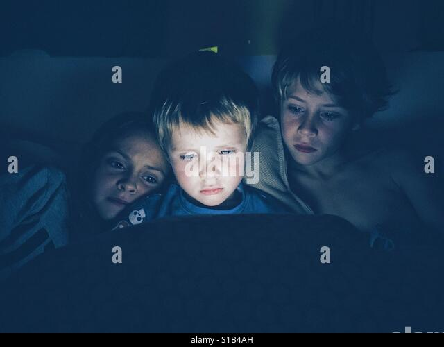 Three young children in the night - Stock-Bilder