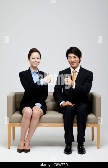 Asian Businessman And Businesswoman  Showing Thumb Up Sign And Sitting On Sofa - Stock Image