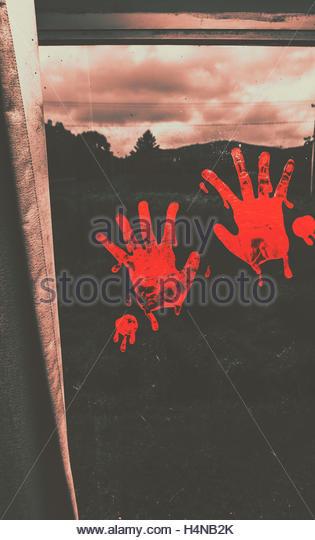 Sinister dark rural scene on blood smeared hand prints splotched on interior window. Mark of murder - Stock Image