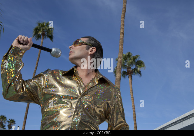 Profile view of middle-aged man posing with microphone - Stock Image