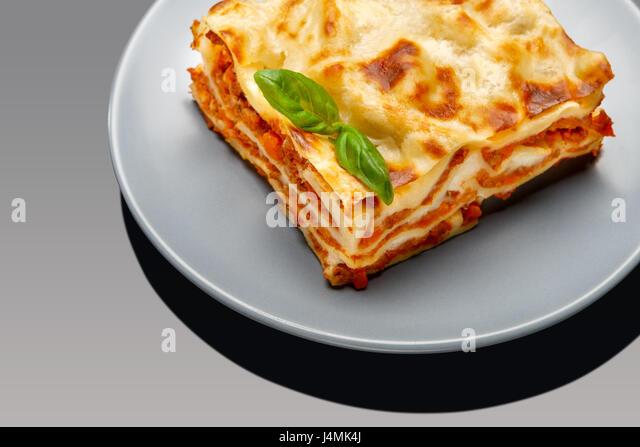 Portion of tasty lasagna on grey background - Stock Image