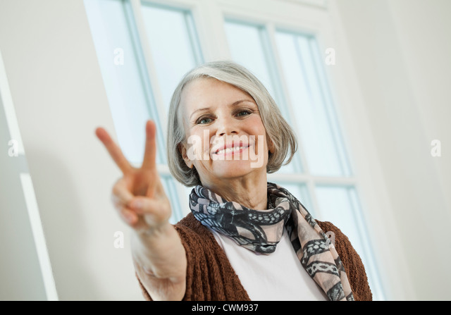 Germany, Berlin, Senior woman showing peace sign, smiling, portrait - Stock-Bilder
