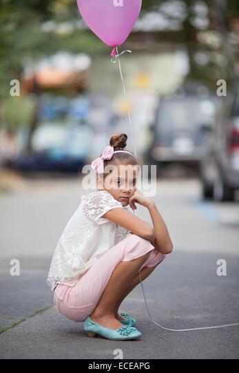 Sad girl (8-9) holding pink balloon - Stock Image